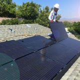 worker adding removing solar panel rooftop roof house